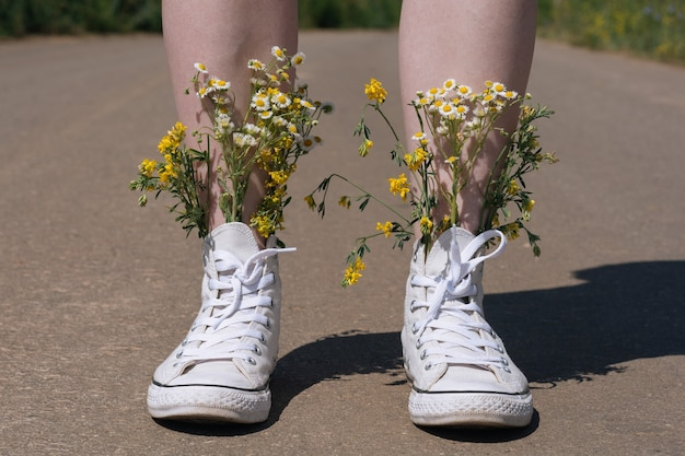 Chaussures baskets blanches marchant sur l'asphalte, chaussures en toile marchant sur du béton