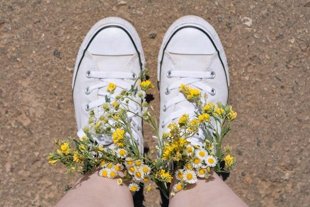 Chaussures de baskets blanches marchant sur la vue de dessus d'asphalte, chaussures de toile marchant sur du béton