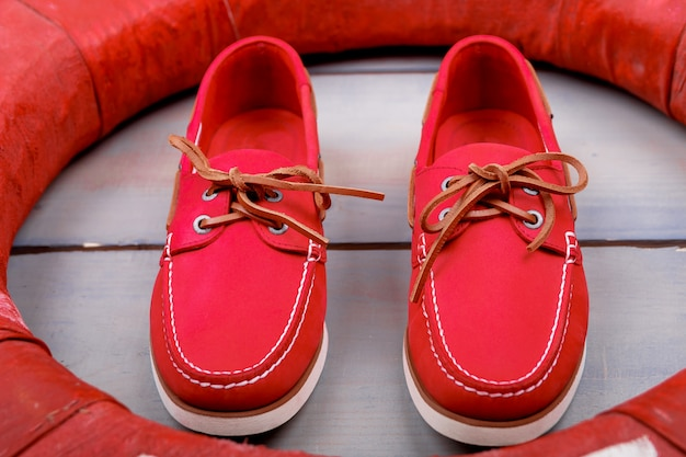 Chaussures de bateau rouge sur fond en bois près de bouée de sauvetage. vue de dessus. fermer