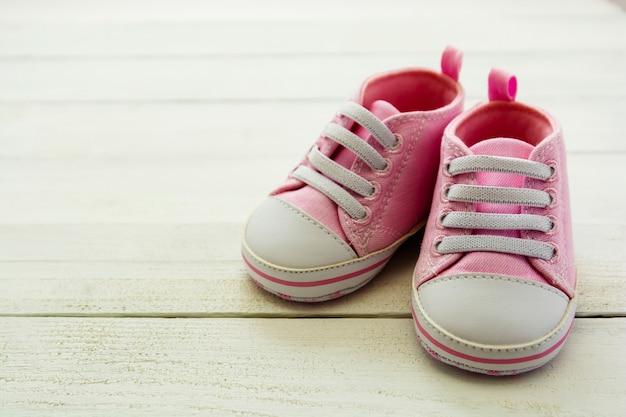 Chaussures bébé fille rose, nouveau-né, maternité, concept de grossesse avec espace copie.
