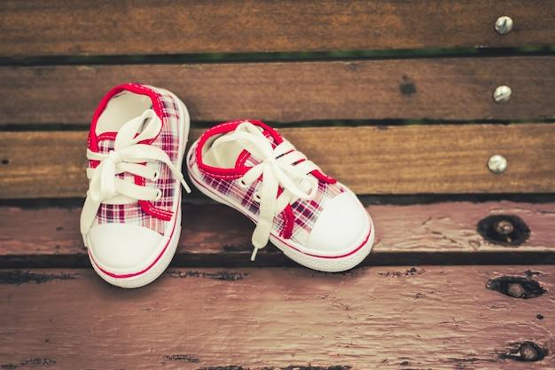 Chaussures bébé rouge et blanc sur une chaise en bois