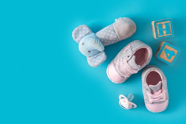 Chaussures bébé, sucette et jouets sur une surface bleue avec espace copie