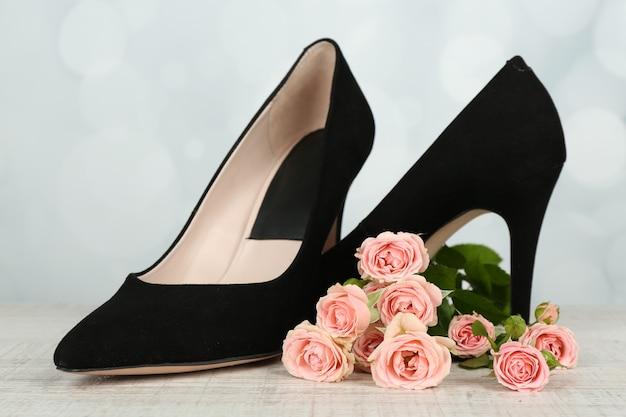 Chaussures de belle femme avec des fleurs sur fond clair