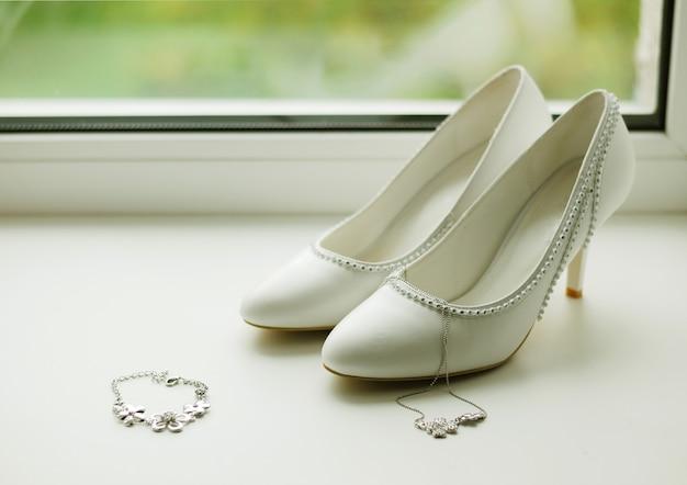 Des chaussures et des bijoux blancs pour femmes sont sur le rebord de la fenêtre. accessoires pour la mariée