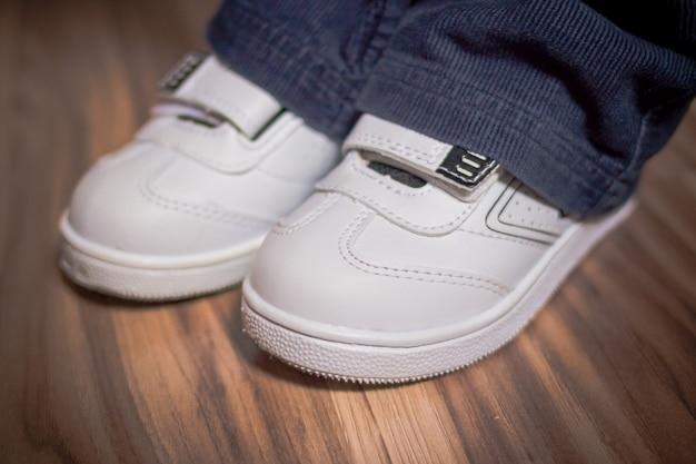 Chaussures blanches modernes, élégantes, à la mode. chaussures pour enfants sur plancher en bois. chaussures pour enfants. mocassins bébé marchant en cuir. chaussure enfant ou chaussures enfant, boots.pair de chaussures blanches stylées pour enfant