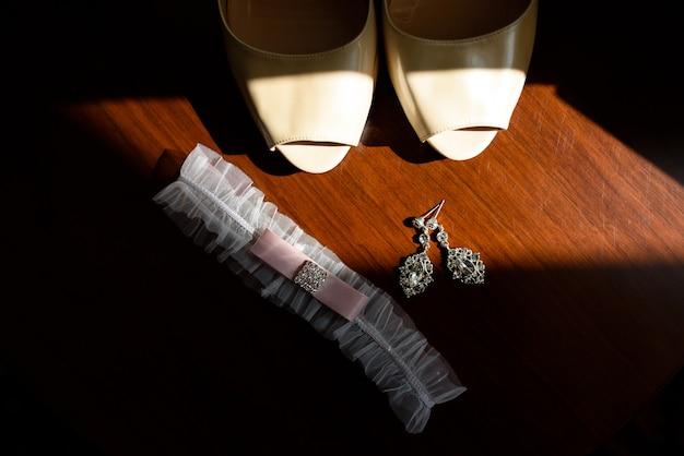 Chaussures, boucles d'oreilles et jarretière pour la mariée.