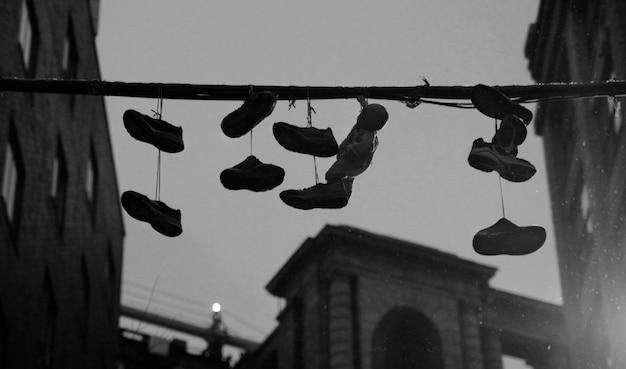 Chaussures sur un câble électrique dans la ville en noir et blanc