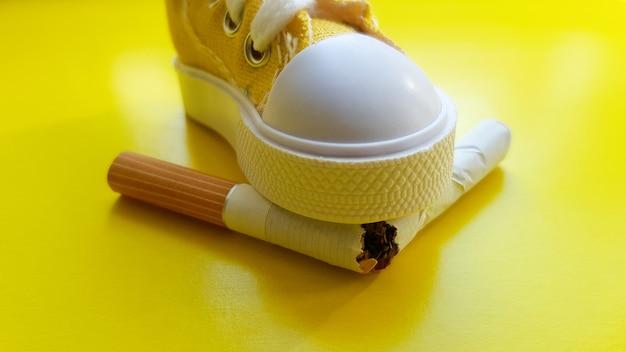 Des chaussures cassent une cigarette sur un espace de copie de fond jaune.