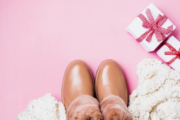 Chaussures chaudes pour femmes en cuir avec fourrure, écharpe blanche et coffrets cadeaux sur fond rose clair. concept de la saison du nouvel an. vue de dessus. faire face à l'espace.