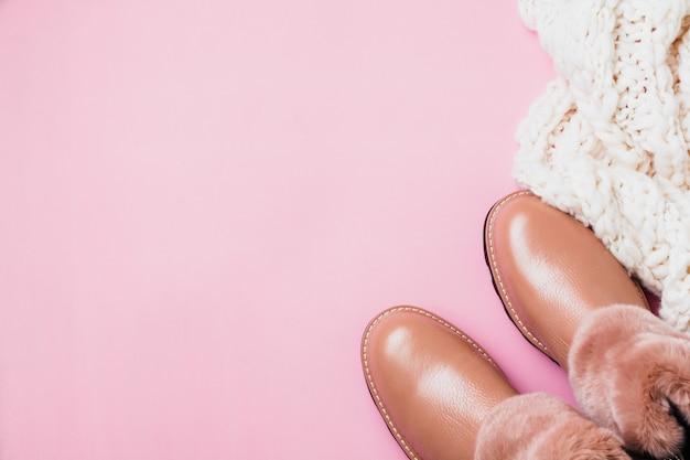 Chaussures chaudes pour femmes en cuir avec fourrure et écharpe blanche sur fond rose clair. vue de dessus. faire face à l'espace.