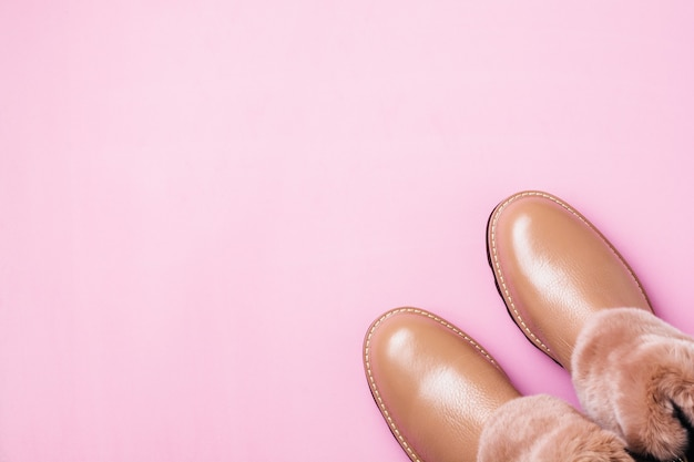 Chaussures chaudes pour femmes en cuir avec fourrure sur fond rose clair. vue de dessus. faire face à l'espace.