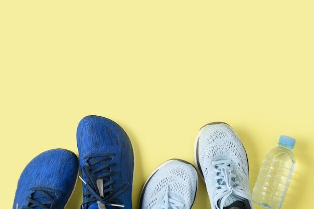 Chaussures de course et bouteille d'eau sur jaune