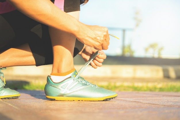 Chaussures de course - femme attachant des lacets de chaussures. gros plan du coureur de remise en forme sport femme se prépare pour le jogging en plein air.