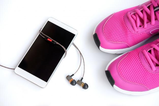 Chaussures de course roses pour femmes, téléphone et écouteurs sur fond blanc