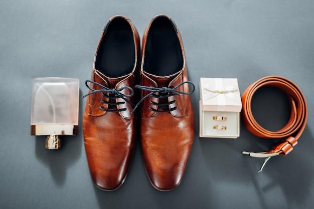 Chaussures en cuir marron, ceinture, parfum et bagues dorées.