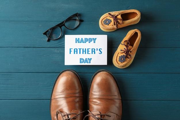 Chaussures en cuir marron, chaussures pour enfants, inscription fête des pères heureuse et lunettes sur fond en bois