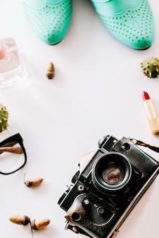 Chaussures en cuir de mode se trouvent avec la caméra, des lunettes et des glands.