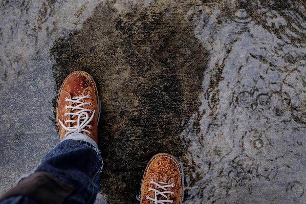 Chaussures en cuir a mouillé en marchant avec parapluie dans la rue dans rainy day