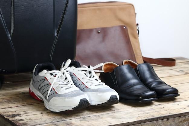 Chaussures en cuir noir, chaussures de sport et sac de voyage pour bagages sur la table en bois.