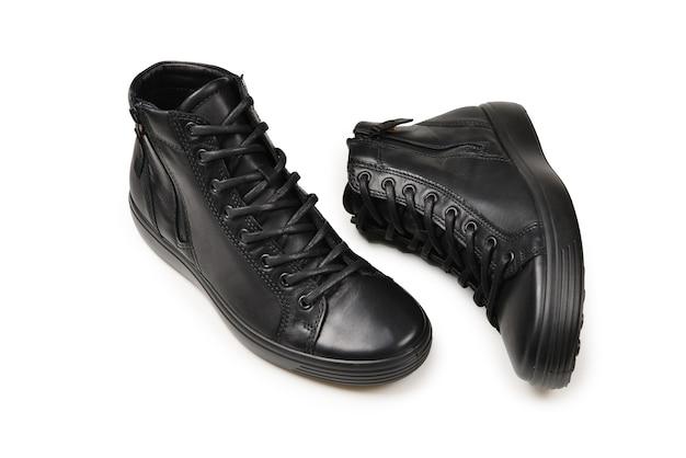 Chaussures en cuir noir pour hommes et un appareil photo noir sur fond blanc isolé. espace de copie.