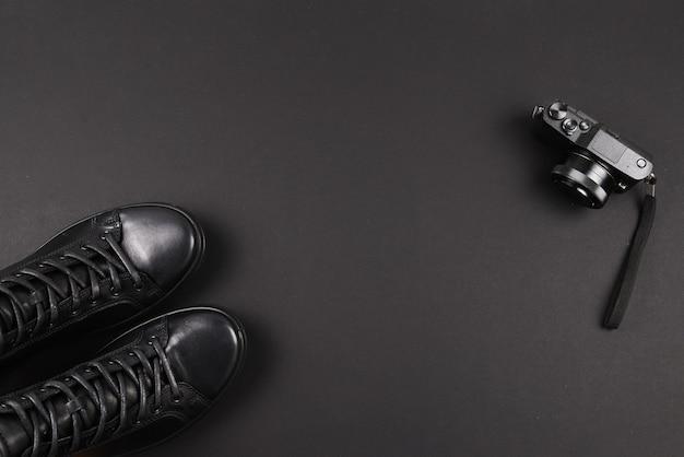 Chaussures en cuir noir pour hommes et appareil photo noir sur fond noir. espace de copie.