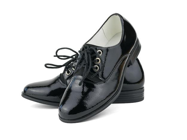 Chaussures en cuir verni à la mode pour femmes noires isolées sur une surface blanche. chaussures d'école à la mode.