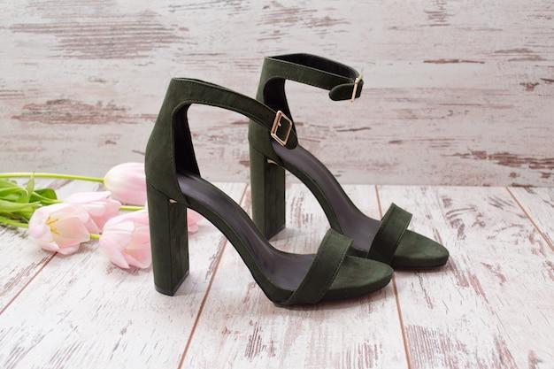 Chaussures en daim vert sur un plancher en bois, tulipes roses