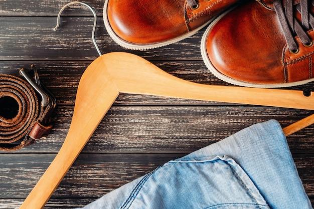 Chaussures décontractées en cuir marron, jean sur cintre et ceinture sur une vue de dessus en bois. concept de mode