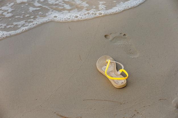 Chaussures avec une empreinte sur la plage.