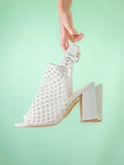Chaussures d'été à la mode pour femmes blanches dans la main d'un enfant sur fond vert. chaussures d'été en cuir pour femmes.