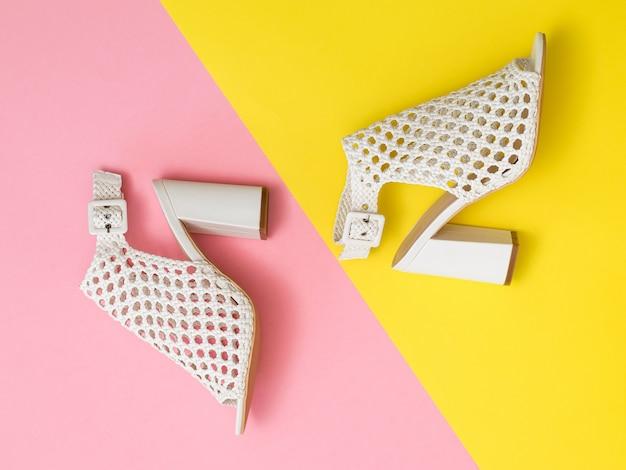 Chaussures d'été à la mode situées en diagonale sur un fond jaune et rose