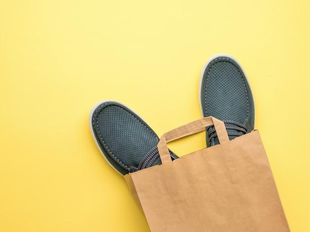 Chaussures d'été pour hommes dans un sac en papier sur fond jaune. acheter des chaussures. mise à plat.
