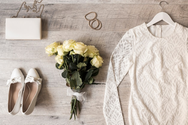 Chaussures habillées; embrayage; chouchous; bouquet de rose et robe de mariée sur fond en bois
