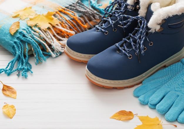 Chaussures d'hiver bleu et gants sur mur en bois blanc