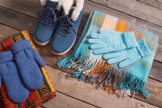 Chaussures d'hiver, gants, foulards sur une vieille table en bois