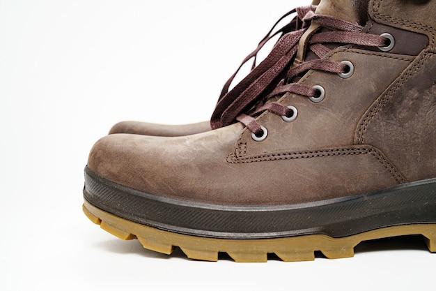 Chaussures d'hiver pour hommes en cuir marron à semelle cannelée sur fond blanc. achetez de belles chaussures modernes pour les voyages et le tourisme.