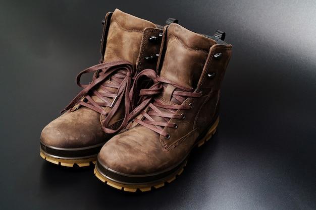 Chaussures d'hiver pour hommes en cuir marron avec semelle cannelée sur fond noir.