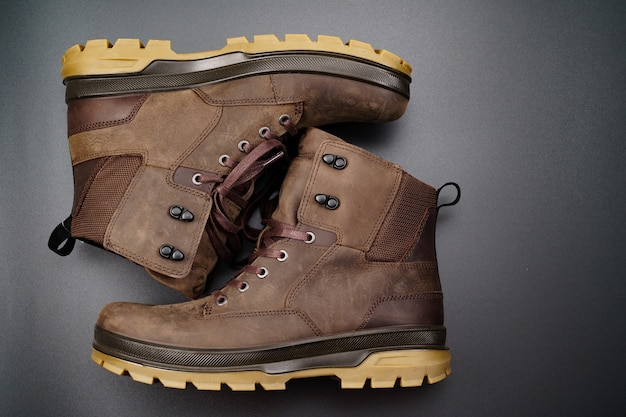 Chaussures d'hiver pour hommes en cuir marron à semelle cannelée sur fond noir.