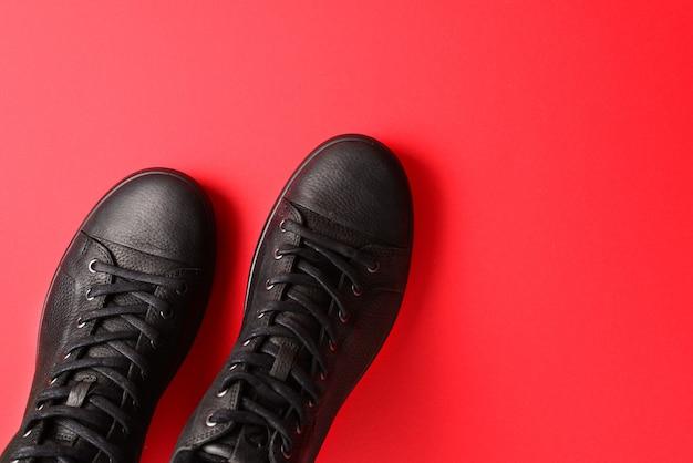 Chaussures homme en cuir noir sur fond rouge.