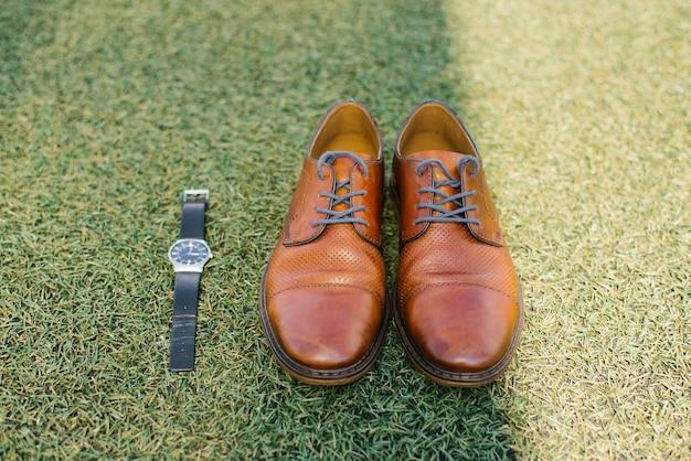 Chaussures homme marron rouge et montre bracelet noire contre l'herbe