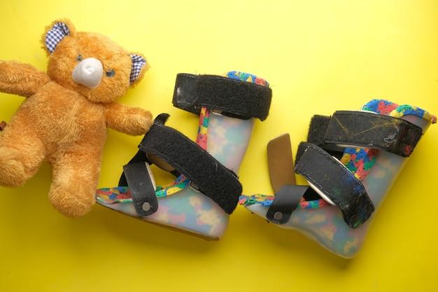Chaussures d'invalidité de paralysie cérébrale d'enfant sur la surface jaune