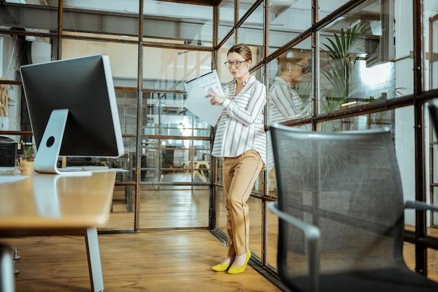 Chaussures jaunes. femme d'affaires enceinte portant un pantalon beige et des chaussures jaunes tout en travaillant au bureau