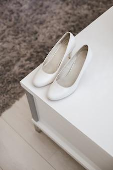 Chaussures de mariage blanches à l'hôtel sur la table.