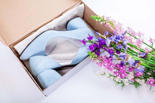 Chaussures de mariage bleu femelle en boîte avec des fleurs sur blanc