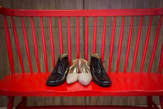 Chaussures de mariage et bouquet sur une chaise rouge pour la cérémonie de mariage