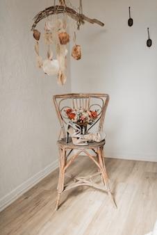 Chaussures de mariage et bouquet de mariée sur une chaise à l'hôtel