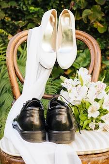 Chaussures de mariage; foulard et bouquet de fleurs sur une chaise en bois