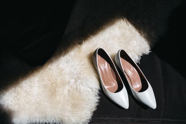 Les chaussures de mariage de la mariée se tiennent sur un canapé
