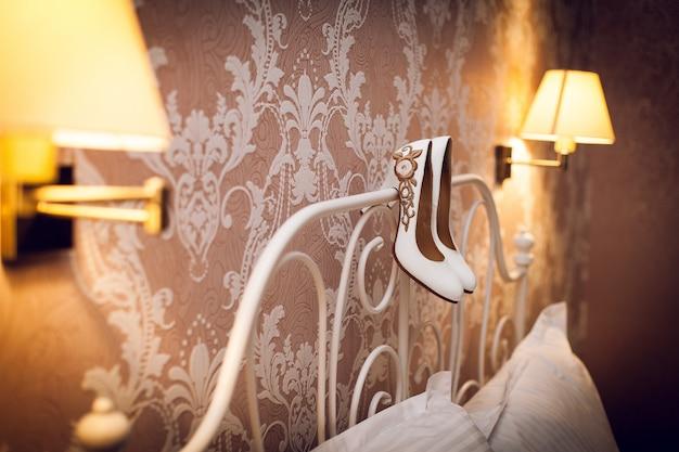 Chaussures de mariée blanche suspendus sur le lit