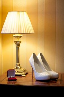 Chaussures de mariée blanches se tiennent à côté d'une boîte rouge avec des alliances en or